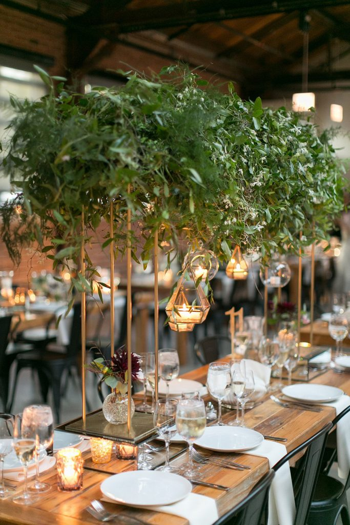 Tall greenery centerpiece with hanging glass globes containing candles on a long rectangular wooden table.