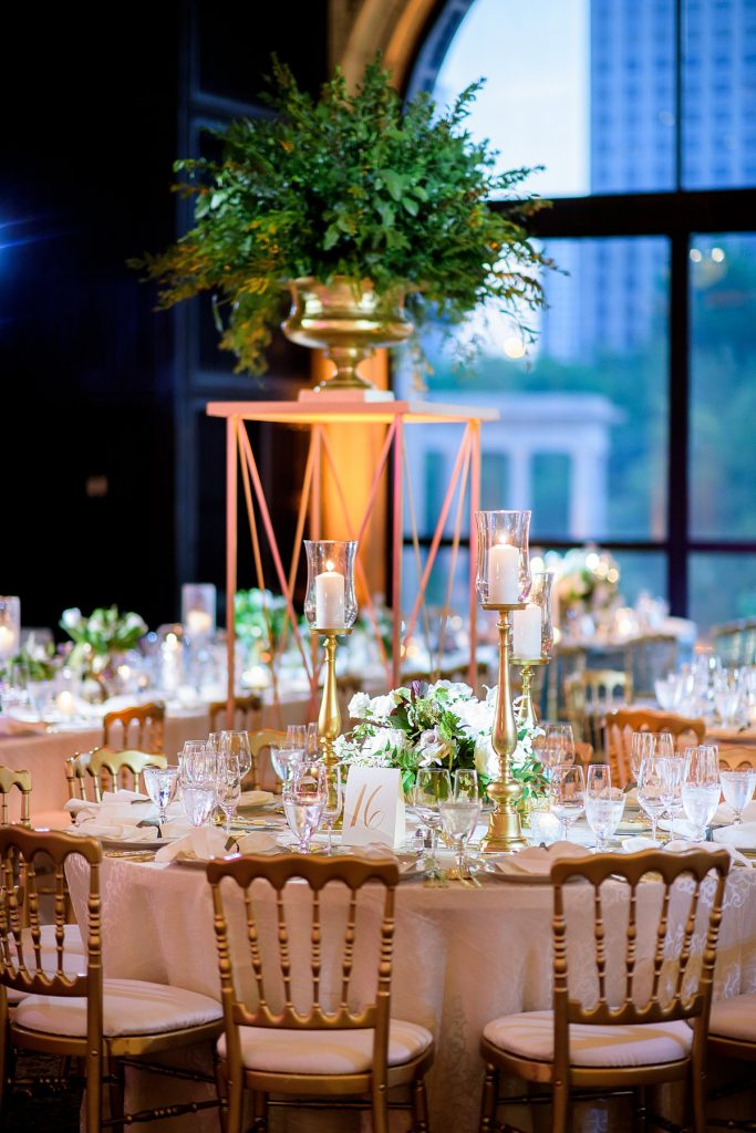 Low floral centerpiece with taller candle trio at a wedding reception table.