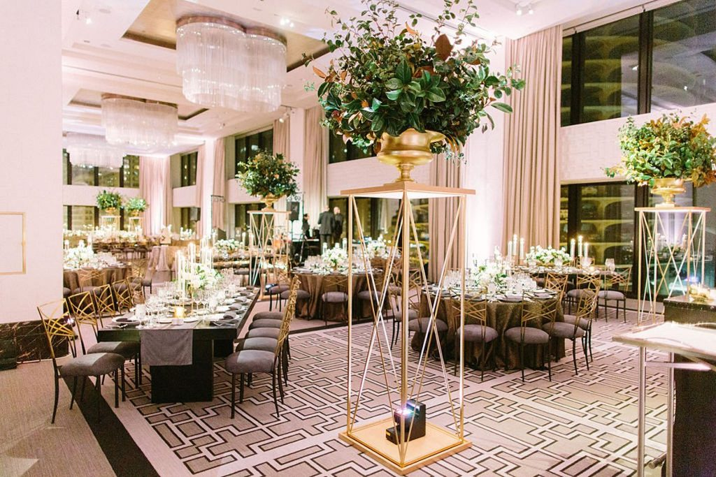 Very large gold, modern pedestal with florals placed throughout the wedding reception room.