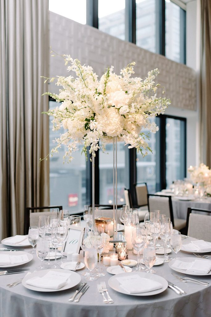 Extra-tall modern centerpiece featuring white florals.