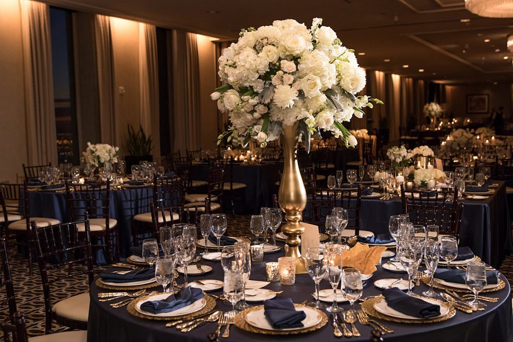 Tall centerpiece at a wedding reception featuring whites and greens in a matte gold vase.