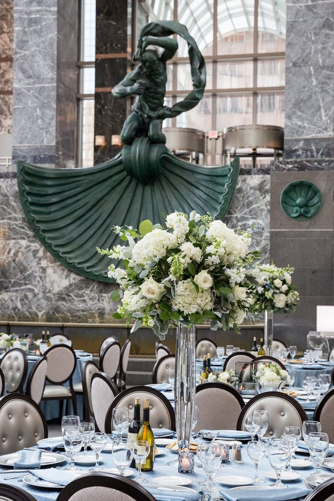 Tall centerpiece at a wedding reception featuring whites and greens.