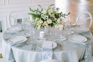 A side profile view of a low floral centerpiece featuring white wedding flowers on a white and light blue tablescape at Company 251. Photo by Tim Tab Studios.