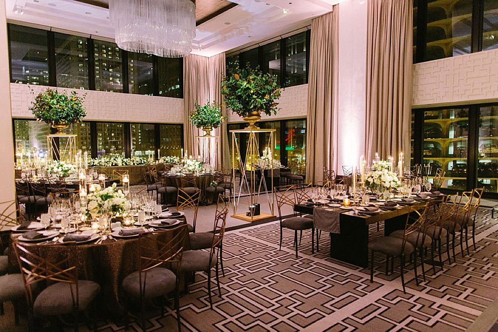 Reception tables at a wedding at The Langham Chicago showcasing XL tall planters throughout the room.