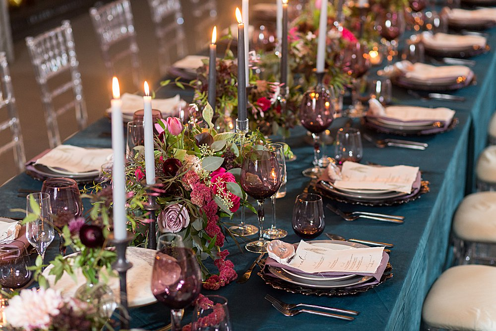 A rectangular wedding reception table featuring dark turquoise linen, a glass place setting, and a lush continuous floral centerpiece with white taper candles.