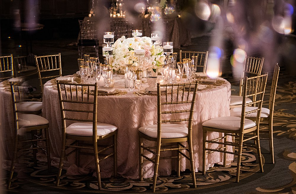 A beautiful wedding reception table with a textured blush linen flowing to the floor. Gold chivari chairs were around the table, and a spotlight shined on a full white-bloomed floral centerpiece.
