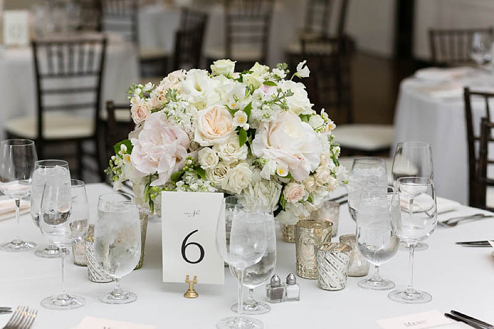White tablescape featuring a small white and blush flowered centerpiece and a white cardstock paper with a black 6 on it. The Table number is held in a gold clip stand.